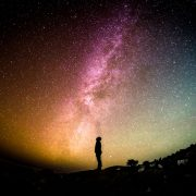 Silhouette of a person looking up at colourful night skies