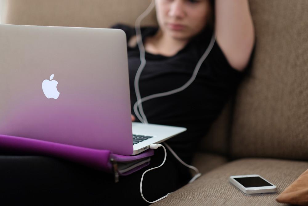 Student in front of laptop wearing headphones